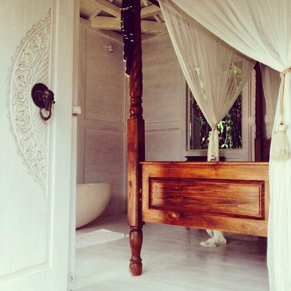 Four Poster Bed overlooking the pool and garden