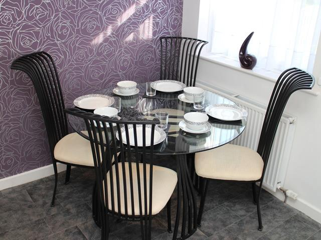 Round glass dining table has seating for 4 people, black iron backed chairs and dinner service for 6