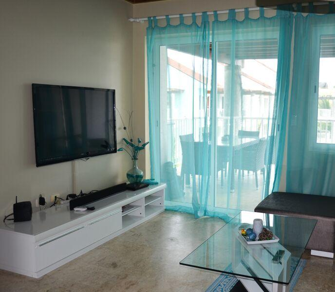 Living area with entertainment center and patio doors to spacious covered balcony