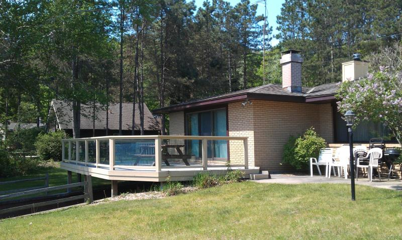 Large deck with glass railings overlooking the lake