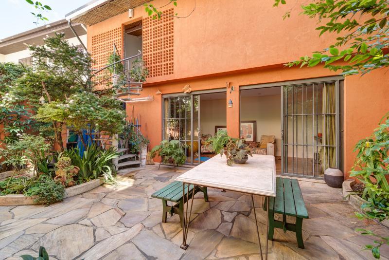 Un patio ajardinado con fuente y aves separa la casa principal de la casa de zorzales