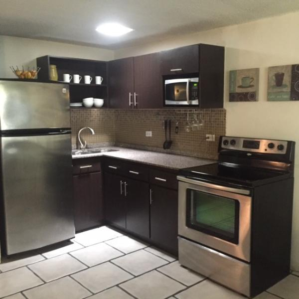 Open kitchen full equipped with stove w/oven, refrigerator & microwave. All you need to cook