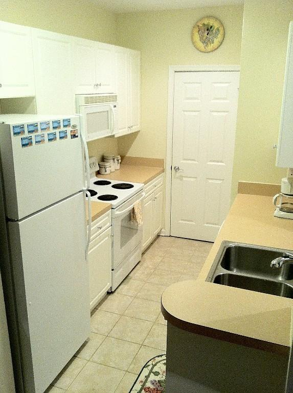 Fully stocked galley kitchen with microwave, dishwasher, coffee maker, toaster