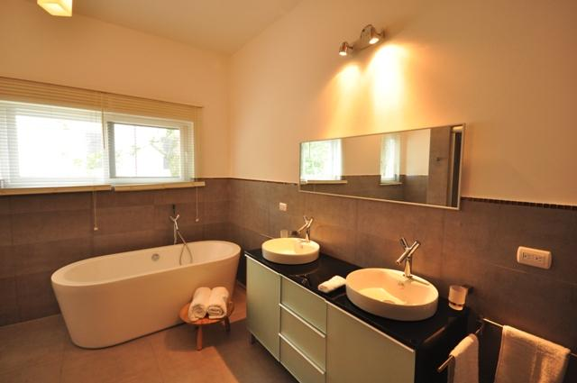 La chambre principale de la salle de bains avec baignoire et son et le sien vanités.