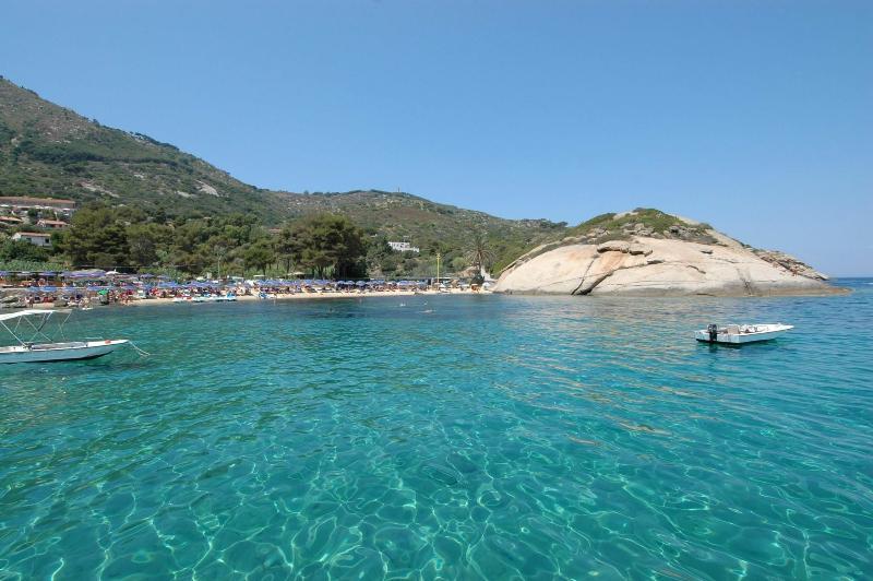 Spiaggia Arenella con l'acqua di colore turchese, trasparentissima e con la Villa