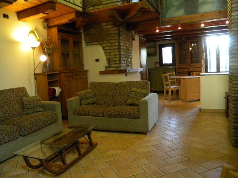 Area soggiorno / living, con divani, scrivania, TV, stereo dolby e cucina all'americana