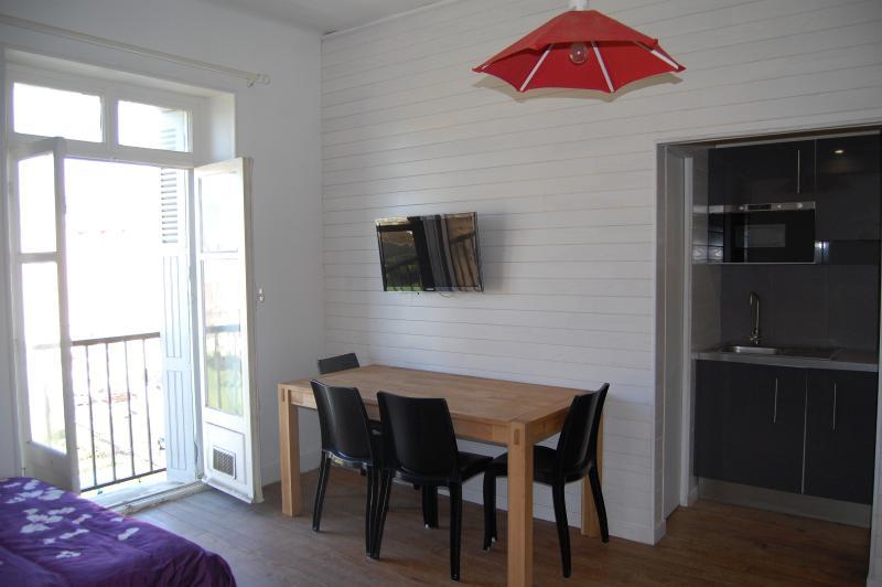 Mesa de comedor y TV de pantalla plana en la pared