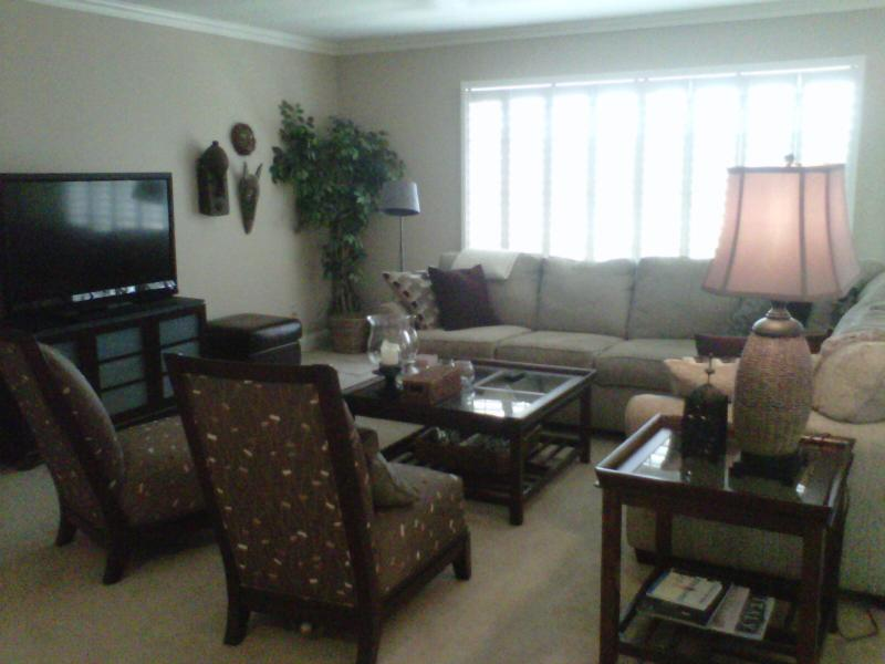 Living room has large comfy L shaped couch, 2 silk chairs, flat screen tv, dvd player & board games