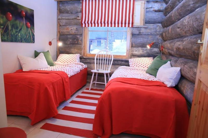 La chambre rouge Puolukka (airelles). Lit peut être défini comme des jumeaux ou un lit double.