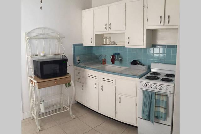 Fully equipped kitchen with stove, microwave, coffee machine and toaster.