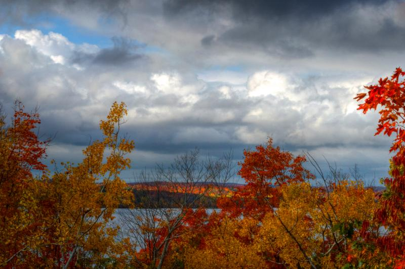 View taken in the fall looking over the colorful foliage to the water and sky beyond