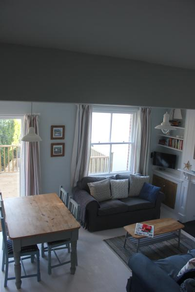 View of Living room from stairs showing French Doors to deck and garden