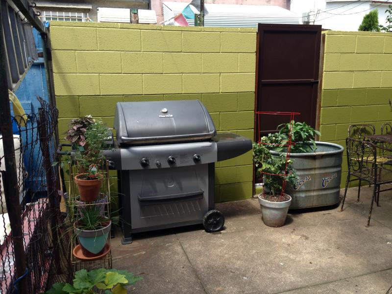 Private patio space with a gas grill, seating for 9 and cozy, cushioned glider.