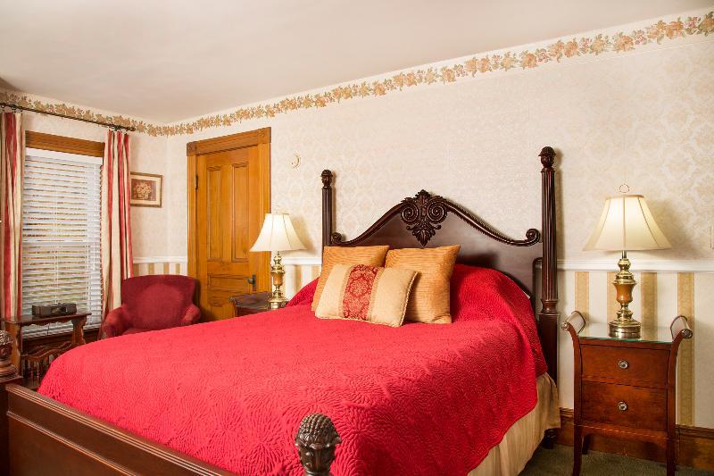 Grant Deluxe Bedroom - queen bed dressed in luxury linens with antique headboard