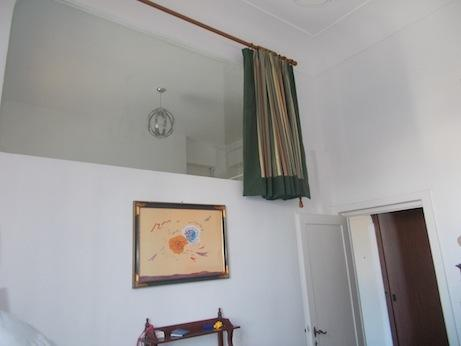 The window in the wall that divides the living room from the bedroom