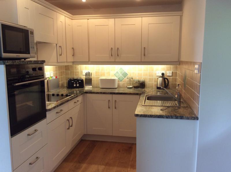 Volledig ingerichte eetkamer keuken met granieten werkblad.