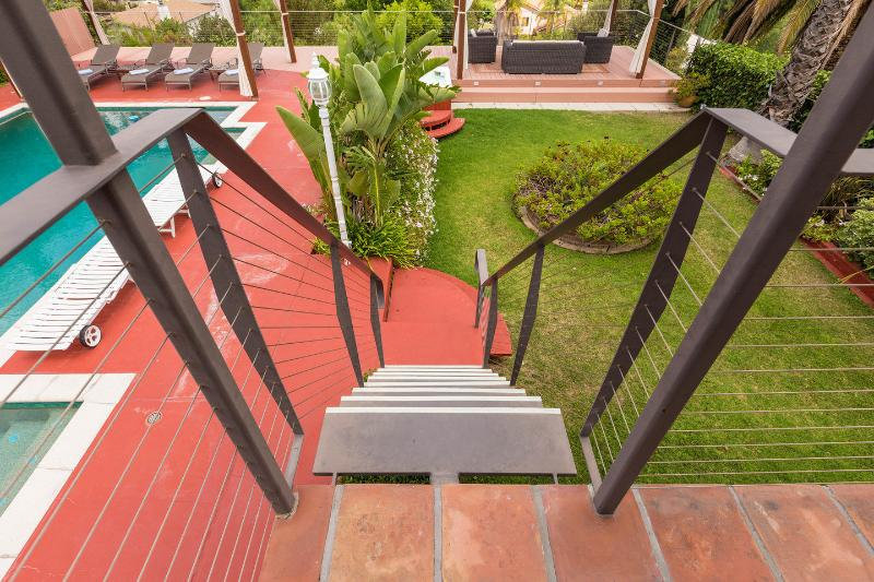 Staircase leading down to the pool area directly from the master suite balcony