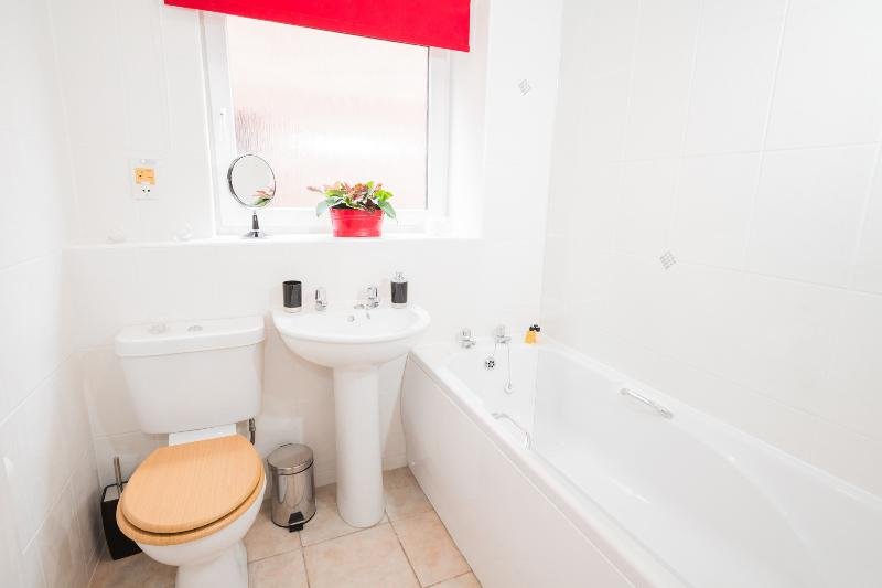 Bathroom with bath and overhead electric shower
