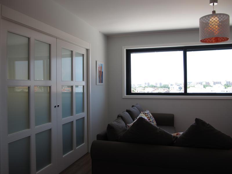 Living room west. At left, door to the kitchen
