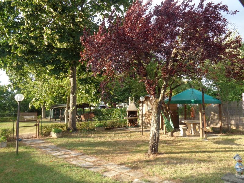 Giardino recintato con barbecue e tavolo in pietra