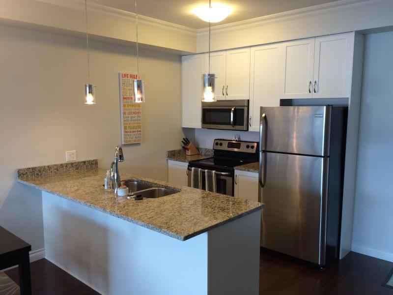 Microwave, Full SS fridge, Cuisinart coffee maker, Professional cookware