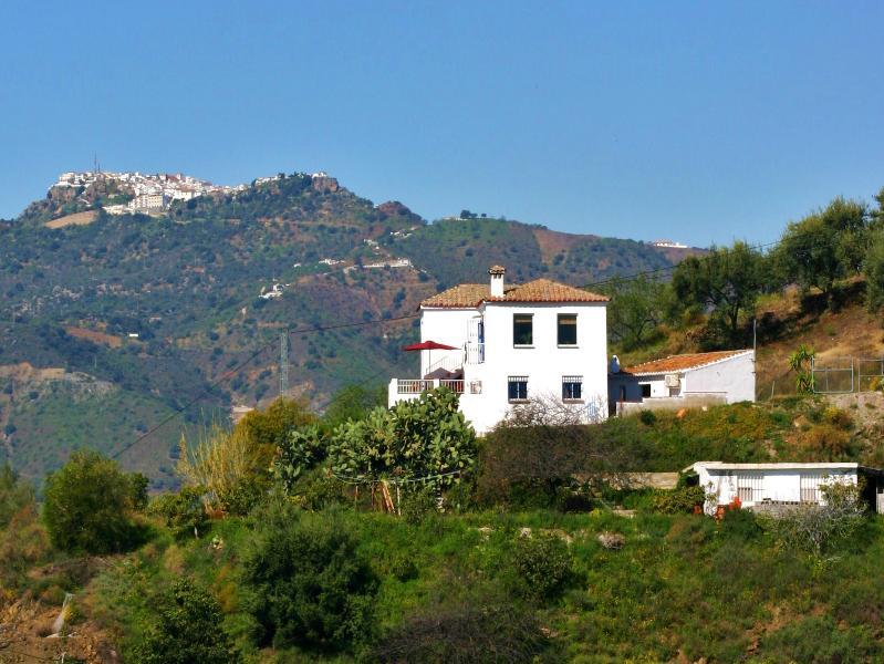 Casa rural 'Encantada' con dos edificios anexos desocupados en Benamargosa. (Comares en el fondo).