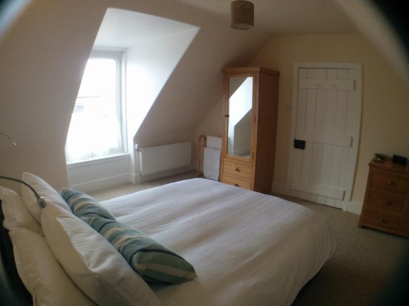 Un luminoso y amplio dormitorio con un rey tamaño