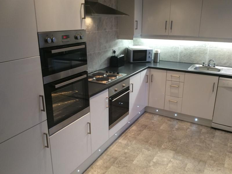 Modern fitted kitchen with eye level double oven, regular fan oven and hob, dishwasher, etc.