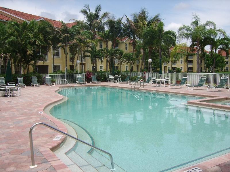 Resort style pool area with heated pool, hot tub, BBQ, and tiki bar