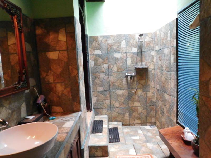 The naturally lit bathroom is fully enclosed
