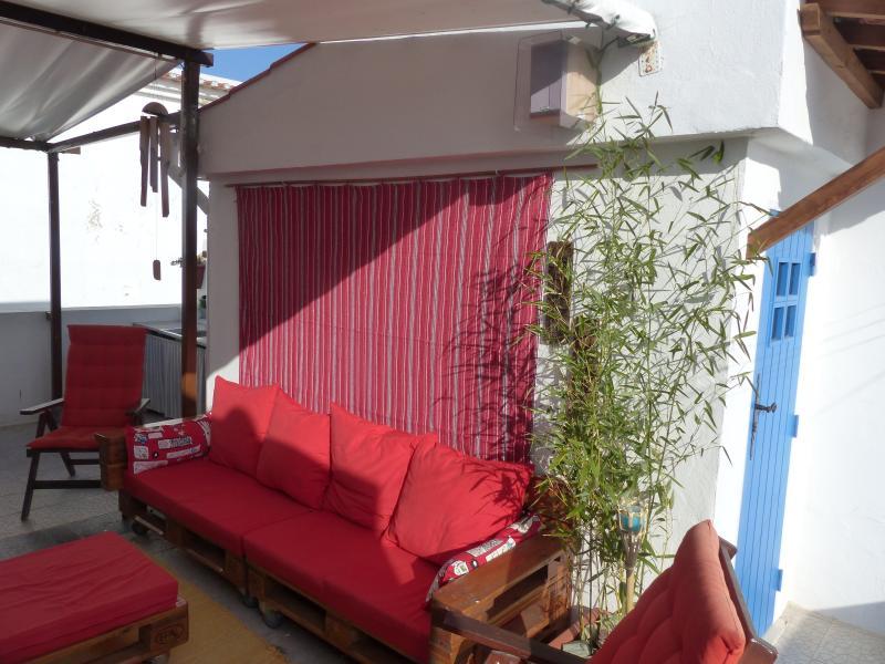 Terraço: Porta de entrada e zona de lazer. Toldo de proteção solar ao longo do terraço.