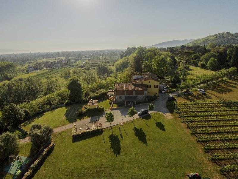 Vista dall'alto della casa, a destra la vigna a sinistra parco giochi, davanti parcheggio e giardino
