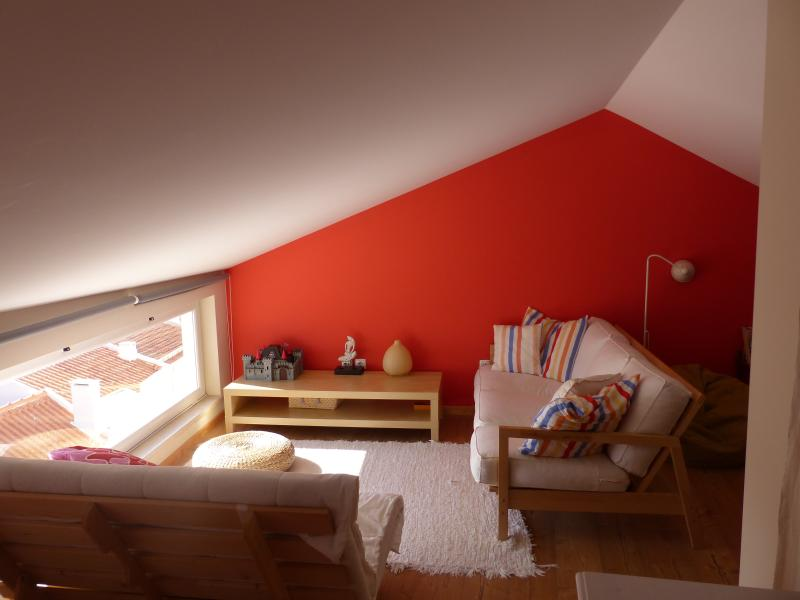 Duplex: zona de repouso com sofá e futon com janelão com vista para o mar e promontório