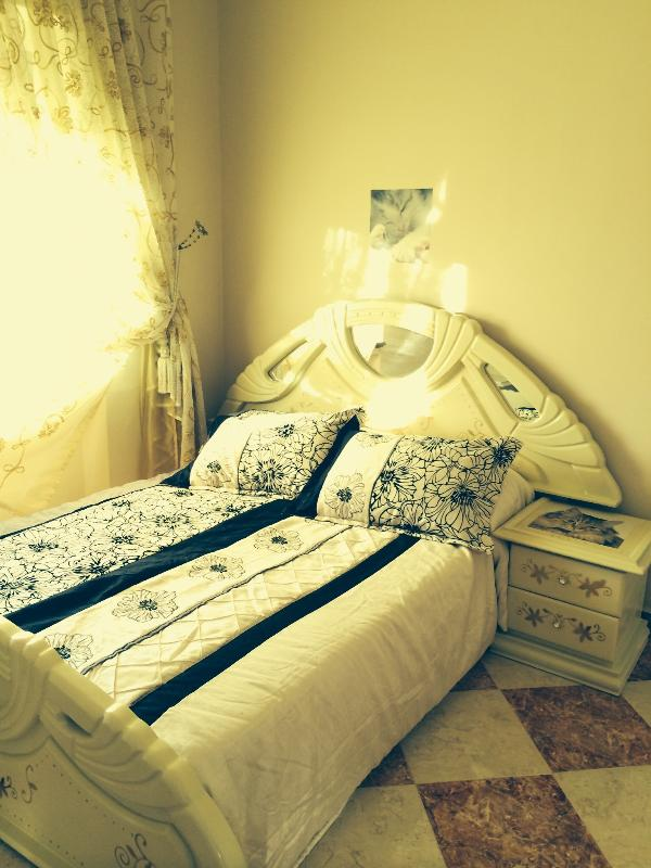 Queen size bed with a dresser and night table.