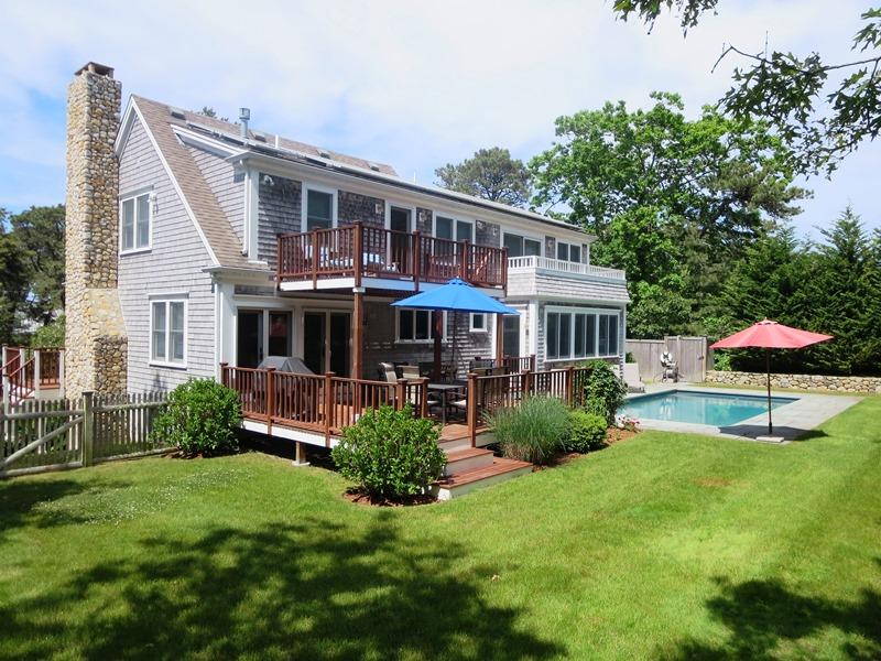 Back of home with multiple decks, outdoor furniture, gas grill, pool and yard - 93 Bucks Creek Road Chatham Cape Cod New England Vacation Rentals