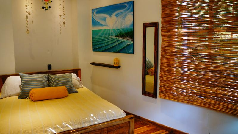 High-quality sheets, handmade furniture and authentic Salvadorian artwork in bedroom #3