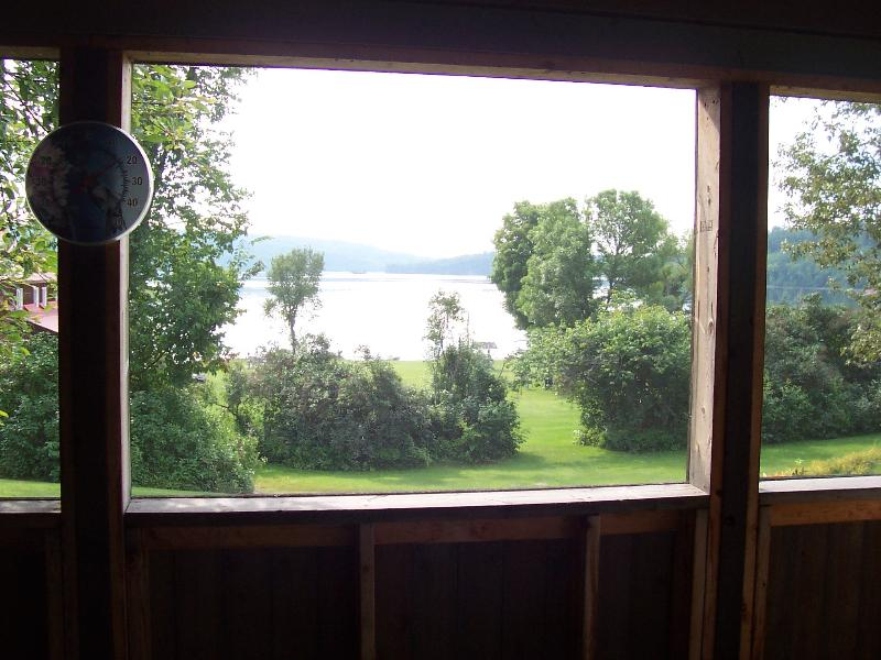 Looking out through a porch screened window towards Norcan Lake.