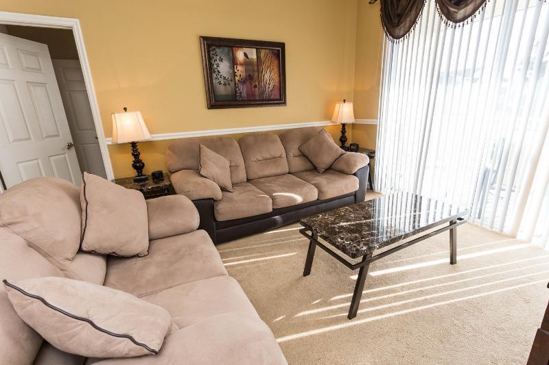 Sala de estar com TV grande tela plana e acesso à varanda