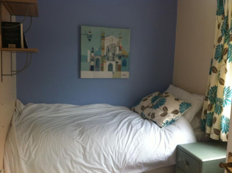 The third bedroom, with a single bed, wardrobe and small chest of drawers.
