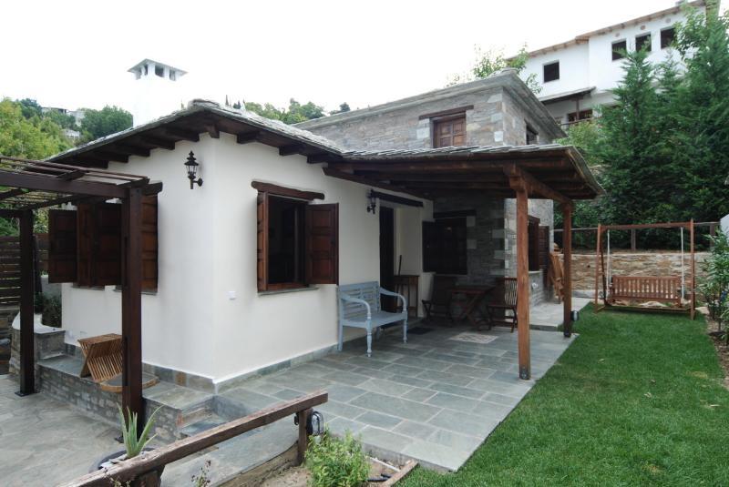 Die Terrasse ist von dem begrünten Garten und die großen Rebe überhängenden die Pergola dominiert