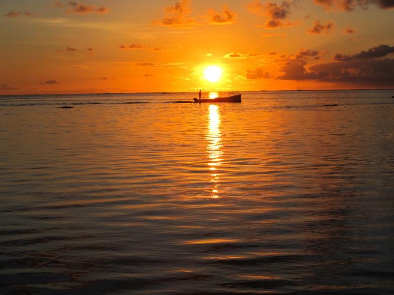 Barco de pesca al amanecer en la laguna de d'Esny Pointe