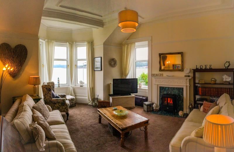 Inviting spacious sitting room with magnifient views, comfortable seating and working electric fire