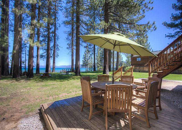 Lakefront home with expansive lawn that leads to pier and private sandy beach.