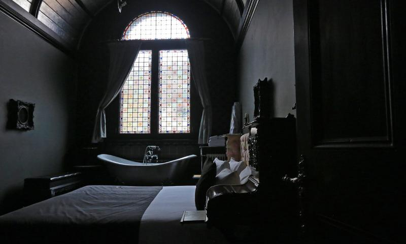 The bedroom of the Chapel Townhouse, with the roll top bathtub and original stained glass window.