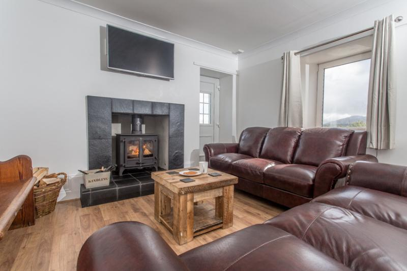 Lounge with leather couches, log burning stove, smart TV & Free Wifi