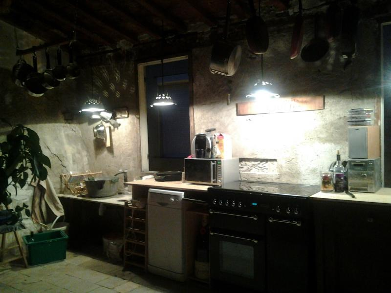 The kitchen area with large fridge/freezer, full cooker, dishwasher and quirky sink and light shades