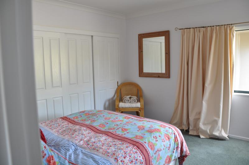 Queen bedroom(2) with shared bathroom and garden views.