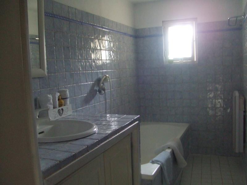 vista cuarto de baño bañera y lavabo. aseo de ropa en cantidad