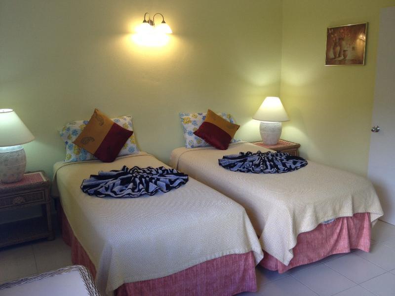 Gasten slaapkamer met 2 enkele bedden, kast, AC, ventilator, En-Suite douchekamer