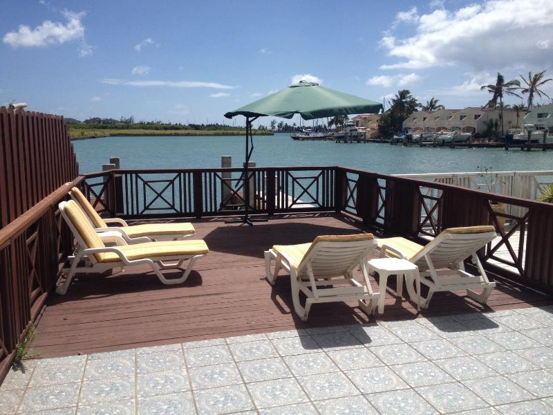 Large patio and deck area with stunning water view south facing, awning, bbq, loungers, dining
